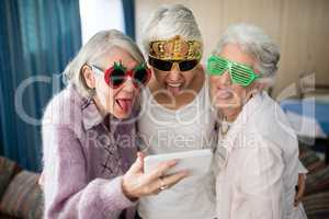 Senior women wearing novelty glasses making face while taking selfie