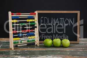 Education text on chalkboard with abacus and green apples