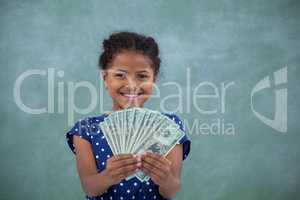 Happy girl showing paper currency