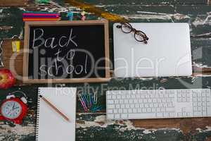 Back to school text written on chalkboard with various stationery, apple and electronics