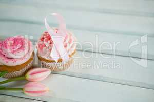 High angle view of Breast Cancer Awareness pink ribbons on cupcakes with tulips