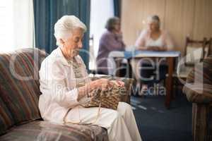 Side view of senior woman knitting while sitting on sofa