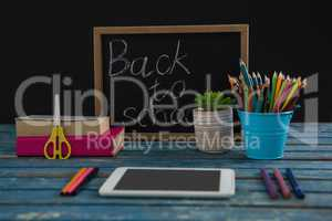 Text on slate with school supplies on tablet