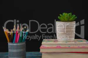 Pot plant, color pencils and book stack on wooden table