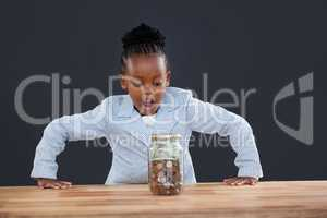 Shock businesswoman looking at coins in glass jar