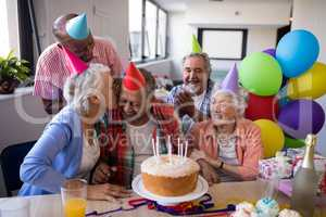 Friend kissing senior man while celebrating at party