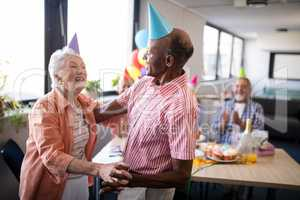 Senior couple wearing party hats dancing at birthday party