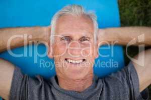 Portrait of smiling senior man lying on exercise mat