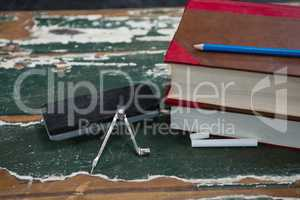 Books, duster and compass on wooden table