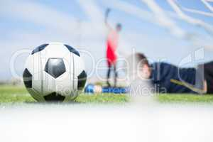 Goalkeeper lying on field while playing soccer