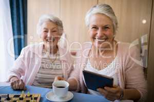 Portrait of smiling senior friends having coffee while playing chess