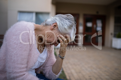 Side view of depressed senior woman sitting on bench with