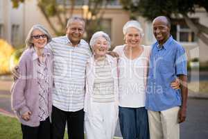 Portrait of cheerful senior people standing with arms around