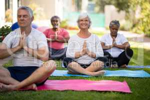 Smiling senior woman meditating in prayer position with friends