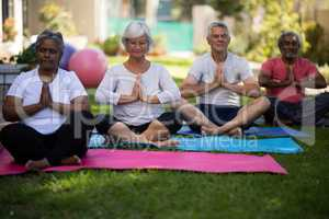 Senior people sitting in prayer position at park