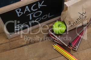 Lunch paper bag, green apple and slate with text back to school on wooden table