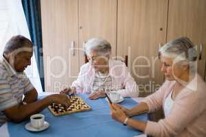 Senior friends playing chess and having coffee