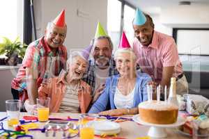Portrait of senior people wearing party hats celebrating birthday