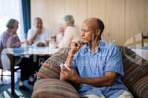 Thoughtful senior man holding mobile phone