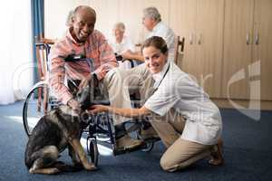 Portrait of smiling female doctor kneeling by disabled senior man stroking puppy