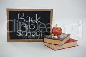 Back to school text with apple and books on white background