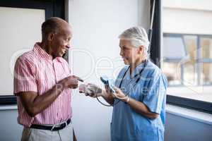 Senior man talking to doctor while pointing at blood pressure