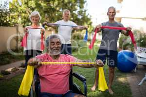 Physically impaired senior man holding ribbon with friends