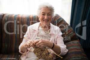 Portrait of smiling senior woman knitting while sitting on sofa against window
