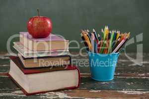 Apple on stack of books with pen holder