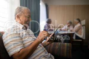 Happy senior man using phone while sitting on sofa