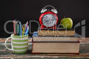 Alarm clock and apple on stack of books with pen holder