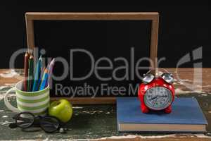 Chalkboard with book, pen holder, apple and spectacles