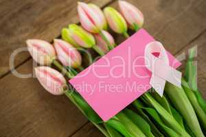 High angle view of pink Breast Cancer Awareness ribbon with blank card on tulips