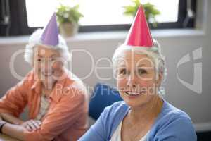 Portrait of smiling senior friends wearing party hats