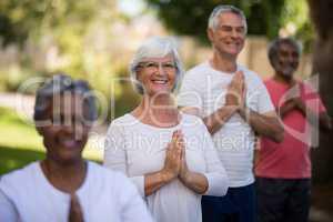 Portrait of senior people meditating in prayer position