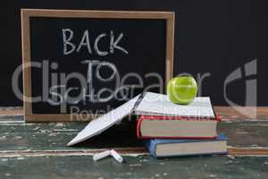 Books, apple and slate board with back to school text