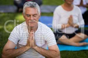 Senior man with eyes closed meditating in prayer position