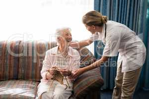 Cheerful senior woman holding knitting wool while looking at female doctor against window