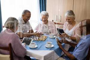 Senior friends playing chess and using technology at table