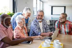 Senior people showing laptop to healthcare worker