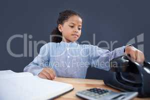 Businesswoman holding receiver of land line phone