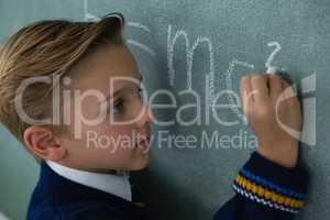 Schoolboy writing maths formula on chalkboard