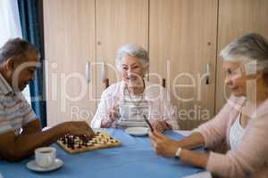 Smiling woman having coffee while sitting with friends