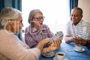 Smiling senior woman showing cards to friends while playing