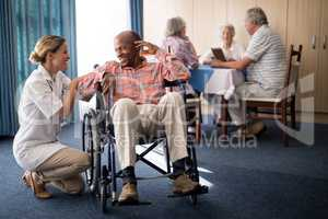Smiling female doctor kneeling by disabled senior man sitting on wheelchair