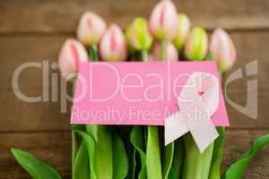 High angle view of pink Breast Cancer Awareness ribbon with blank card on fresh tulips