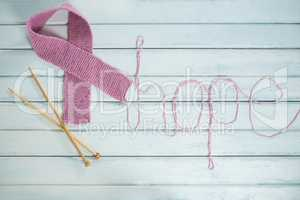 Overhead view of pink Breast Cancer Awareness ribbon by hope text and crochet needles