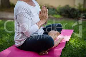 Low section of senior woman meditating in prayer position