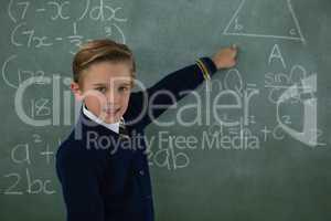 Schoolboy solving maths formula on chalkboard