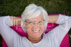 Portrait of smiling senior woman lying on exercise mat